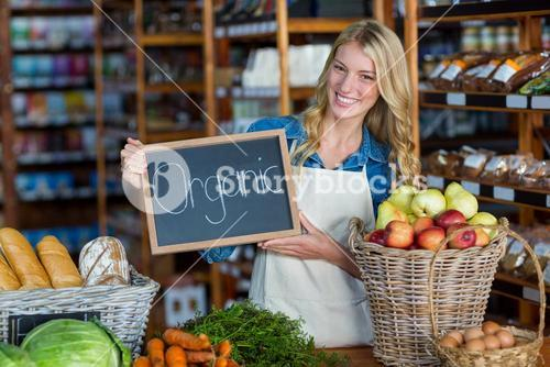 Smiling staff holding organic sign board in organic section