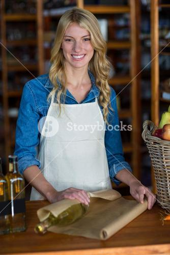 Smiling female staff wrapping olive oil bottle with brown paper