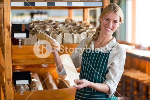 Female staff packing a bread in paper bag