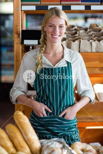 Smiling female staff standing at bread counter