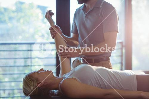 Woman receiving hand therapy exercises from physiotherapist