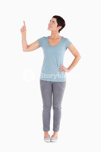 Darkhaired woman pointing at copy space