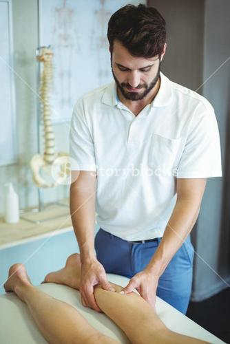 Physiotherapist giving leg massage to a woman