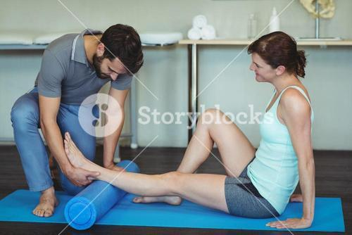 Physiotherapist giving leg massage to a woman on exercise mat