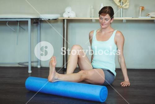 Woman performing exercise using foam roll