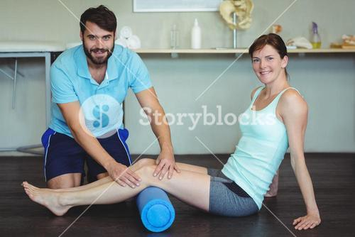 Physiotherapist doing leg therapy to a woman using foam roll