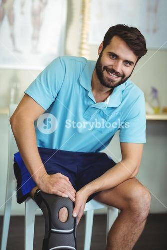 Portrait of smiling man with knee injury