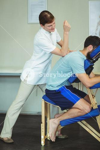 Physiotherapist giving back massage to a patient