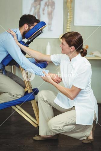 Physiotherapist giving arm massage to a patient