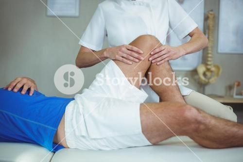 Physiotherapist giving foot massage to a patient
