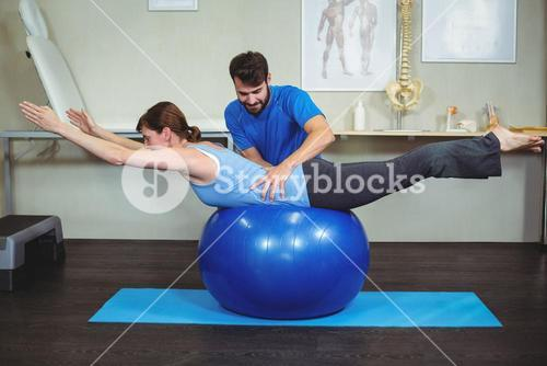 Physiotherapist assisting woman on exercise ball
