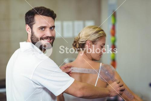Male therapist measuring female patient back with goniometer