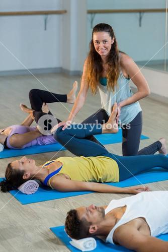 Yoga instructor helping student with leg flexes