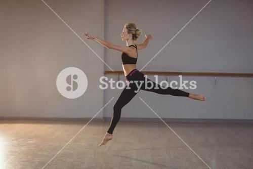 Woman leaping while performing stretching exercise