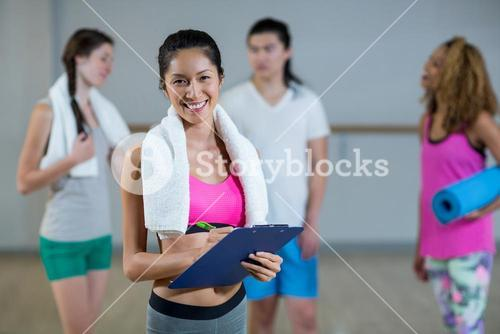 Portrait of female trainer holding clipboard