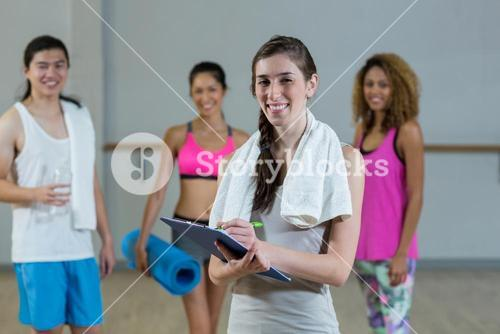 Portrait of female trainer holding clipboard with fitness class in background