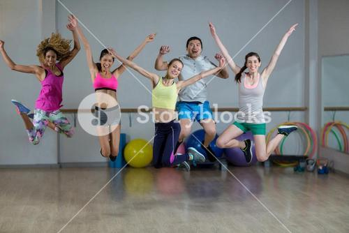 Group of fitness team jumping in fitness studio