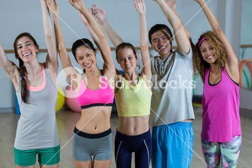 Group of fitness team posing with arms up in fitness studio