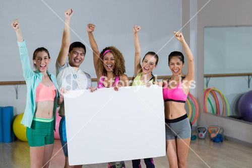 Group of fitness team holding blank placard and clenching fists