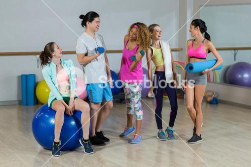 Group of fitness team interacting in fitness studio