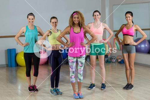 Portrait of group of fitness team standing with hands on hip