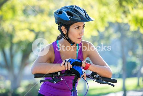 Female athletic leaning on bicycle in countryside
