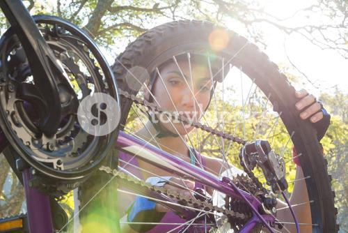 Female cyclist repairing her bicycle in park