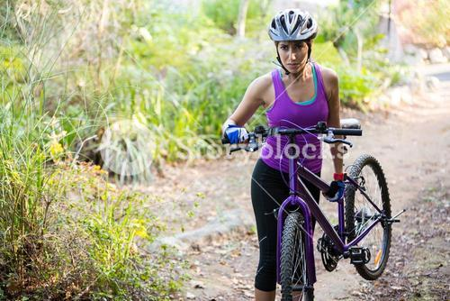 Female cyclist carrying mountain bike while walking