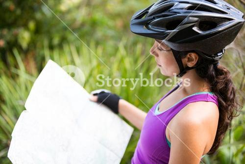 Female cyclist looking at map