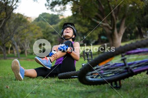Female cyclist getting injured while falling from mountain bike