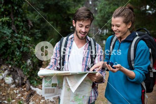 Hiker couple looking at map and compass
