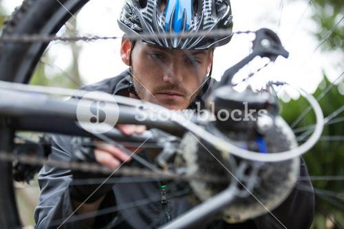 Male cyclist repairing his mountain bike