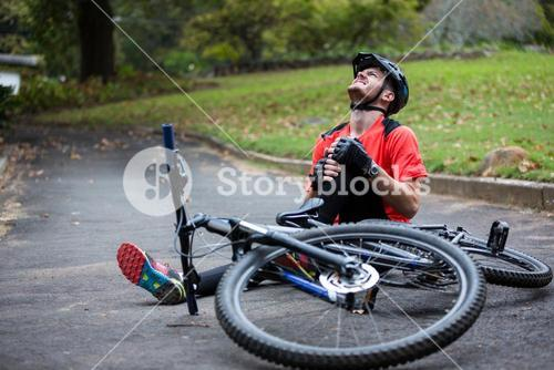 Male cyclist getting injured while falling from mountain bike