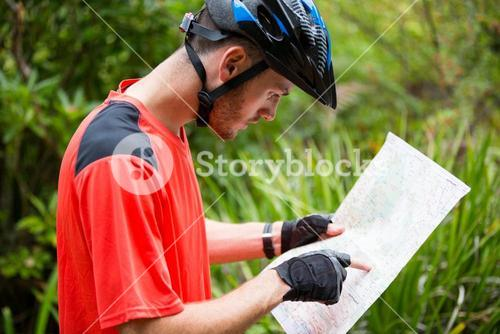 Male cyclist looking at map
