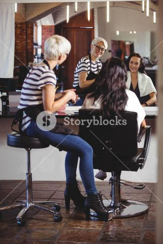 Hair stylist sitting with client at the hair salon