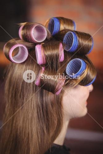 Woman with hair roller on hair