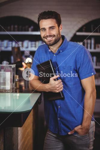 Portrait of male hairdresser holding a diary at the hair salon