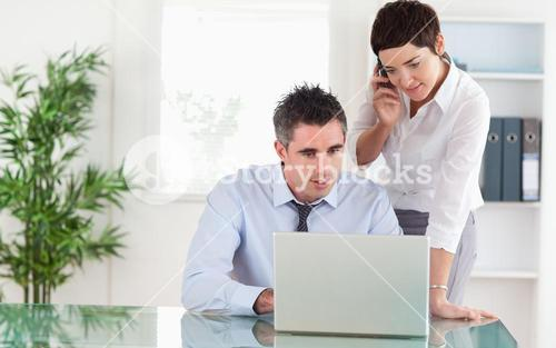 Colleagues working with a laptop and a cellphone