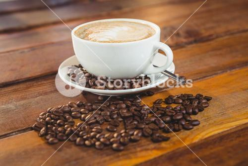 Cappuccino with coffee beans on table