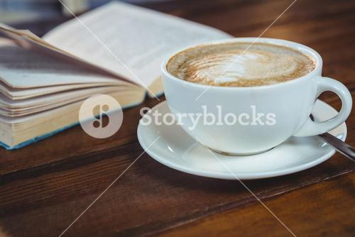 Cappuccino and book on table