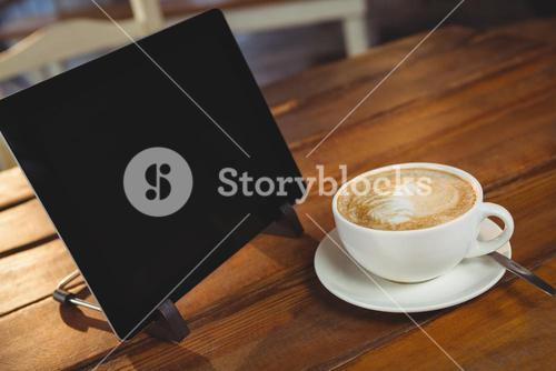Cappuccino and digital tablet on table