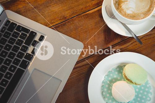 Cappuccino, laptop and sweet food on table