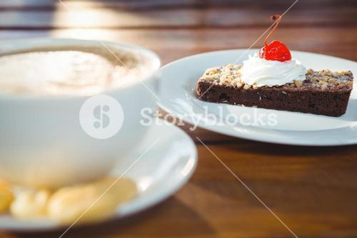 Pastry with whipped cream and cherry topping on table