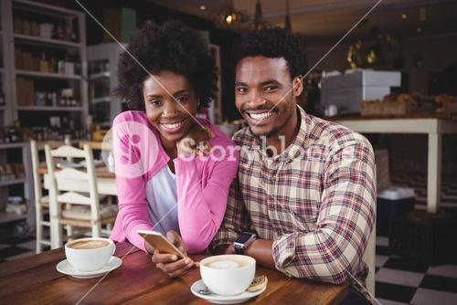 Young couple using mobile phone in cafeteria