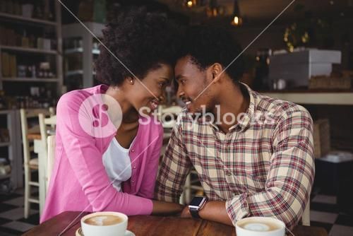 Young couple romancing while having coffee