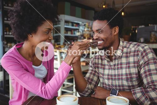 Young couple feeding each other