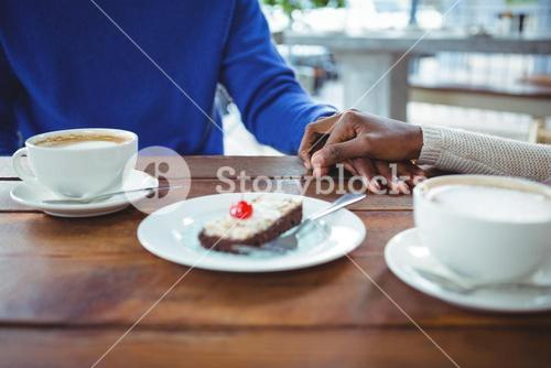 Couple holding hands while having coffee