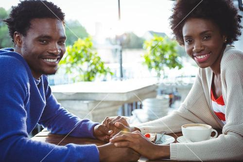 Young couple holding hands while having coffee