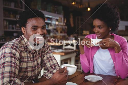 Young couple having coffee in cafeteria