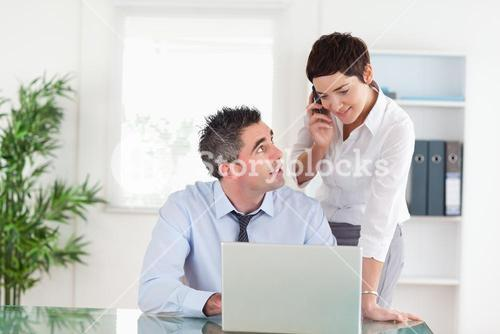 Businesswoman making a phone call while her colleague is working on a laptop